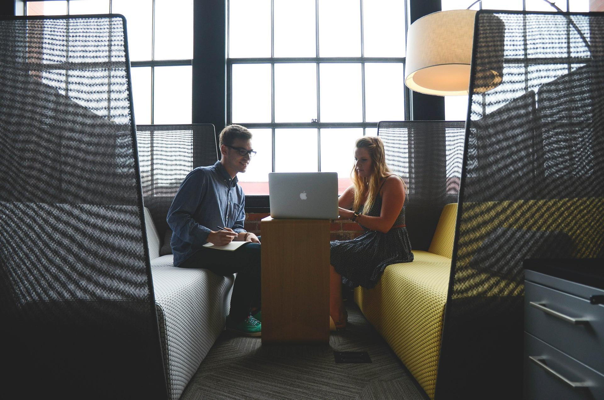 mand og kvinde ved bord med computer