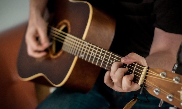 spille guitar